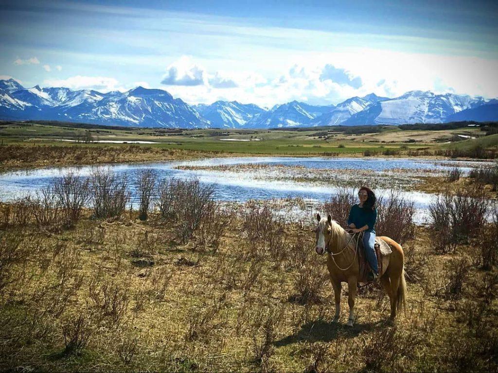 Kim on horse with mountain backdrop